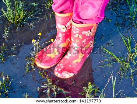 Child girl legs in pink galoshes standing inside a puddle of water - stock photo