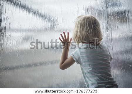 Child girl looking at raindrops on the window
