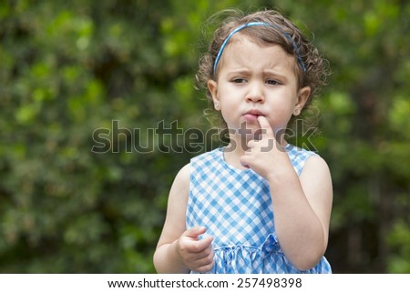 child girl looking thinking with finger at mouth - stock photo