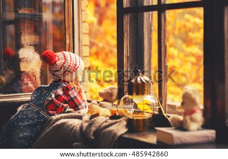 child girl looking through the open window at the beautiful nature autumn gold