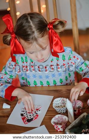 child girl making christmas handmade post card at home - stock photo