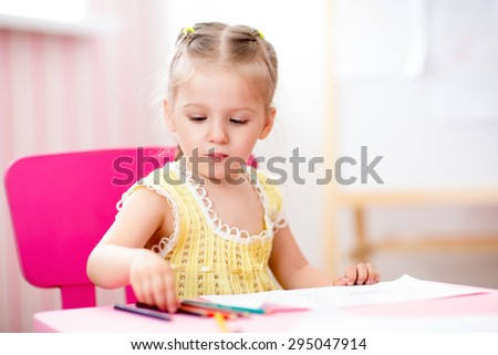 child girl painting in nursery at home - stock photo