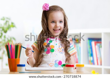 child girl paints in her nursery at home - stock photo