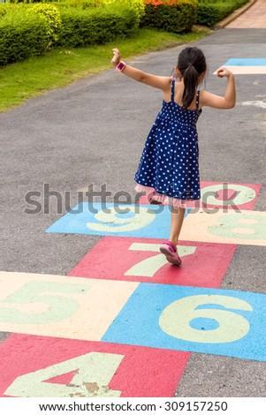 Child Girl Playing Hopscotch on Playground - stock photo