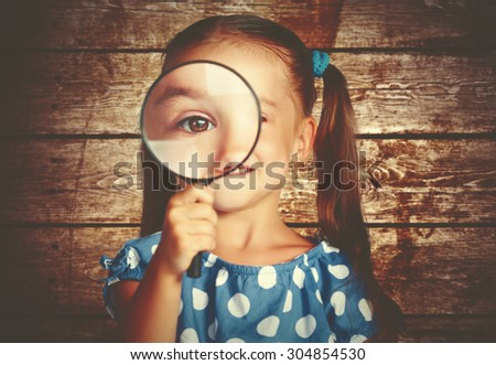 child girl playing with a magnifying glass in the detective - stock photo
