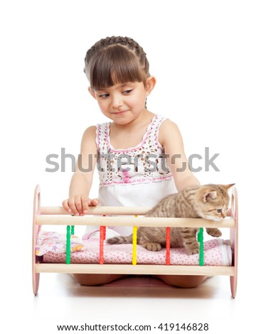 Child girl playing with cat kitten and rocking him in doll crib