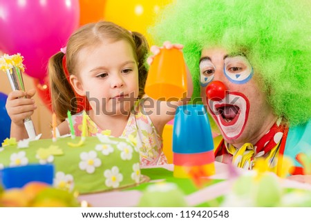 child girl playing with clown on birthday party - stock photo