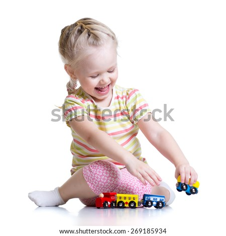 child girl playing with color toys isolated on white