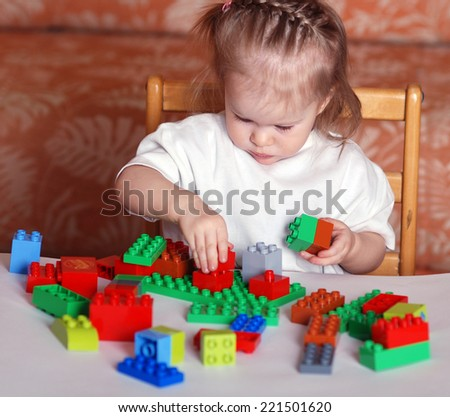 child girl playing with colorful buiding block toys - stock photo