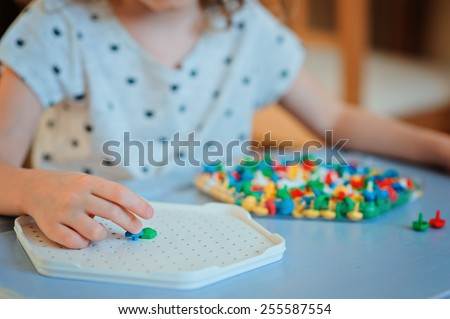 child girl playing with colorful plastic mosaic at home on blue table - stock photo
