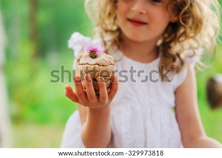 child girl playing with salt dough cake decorated with flower, summer crafts on vacation - stock photo