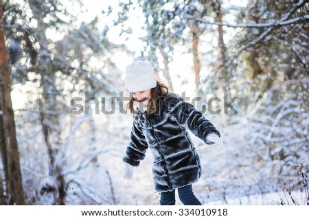 child girl playing with snow on the walk in snowy winter forest. Outdoor activity on winter holidays. - stock photo