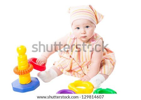 Child girl playing with  toy pyramid build from rings isolated on white background