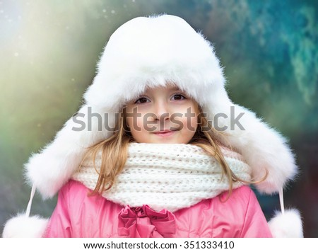 Child girl portrait in hat scarf outdoor winter season.Kid's fashion.Smiling caucasian toddler on nature background. - stock photo