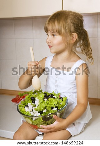 Child girl preparing greek salad, little girl preparing and eating vegetable salad - stock photo