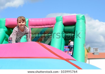 Child girl's fun on inflatable playground - stock photo