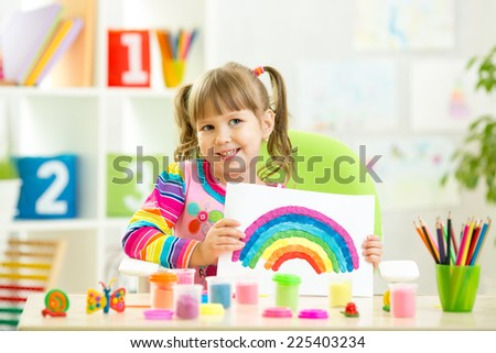 child girl showing plasticine rainbow making by her hands - stock photo