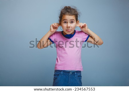 child girl showing tongue pulls ears on gray background