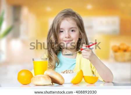 Child girl sitting at table eating breakfast indoors. Kid's healthy nutrition concept.Female toddler have a meal of cereal,buns, oranges and juice. - stock photo