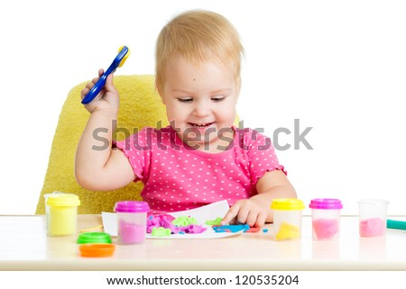 Child girl sitting at table playing with colorful clay