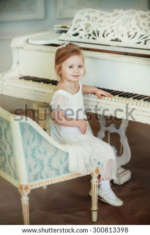 child girl sitting near the white piano - stock photo