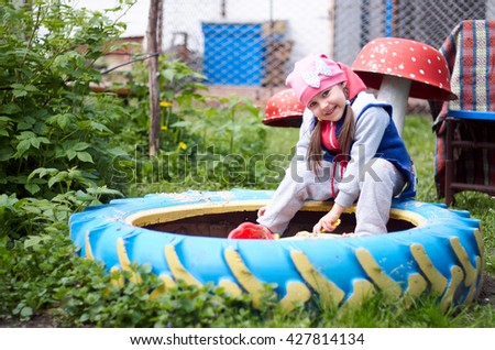 Child girl sitting outdoors in courtyard of kindergarten. Happy kids playing in sand playpit/Adorable little girl having fun playing outdoors on summer day - stock photo