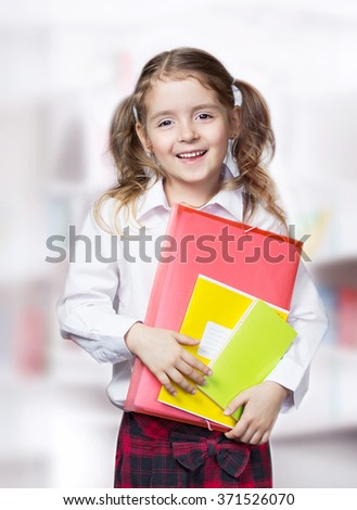 Child girl smiling stand hold folder book in white shirt. Pupil education concept. - stock photo