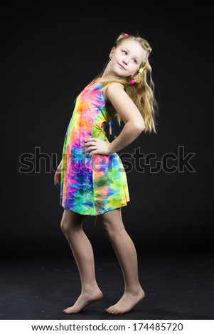 Child girl standing posing in colorful dress in studio black background