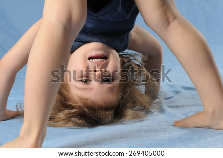 Child girl upside down in studio, she stands on her head and looking at camera with smile - stock photo