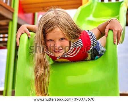 Child girl upside down on  park playground game. Girl slides on children's slide. - stock photo