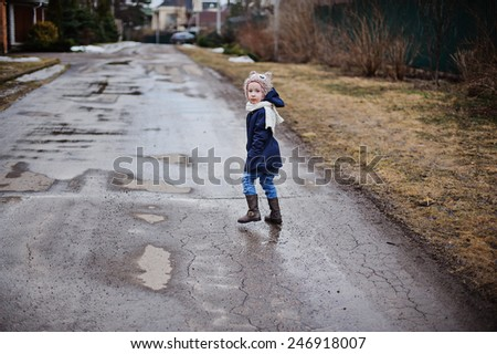 child girl walking on the road in early spring