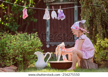 child girl washing her doll in summer garden - stock photo