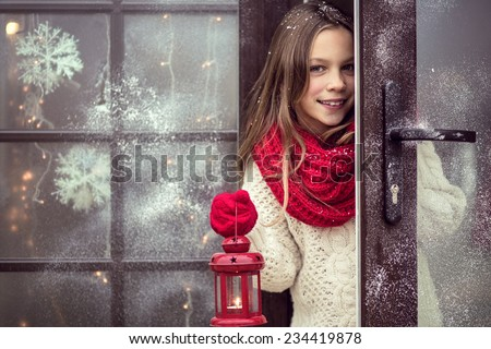 Child girl welcome guests and holding holiday lantern, snow weather, house is decorated before Christmas - stock photo