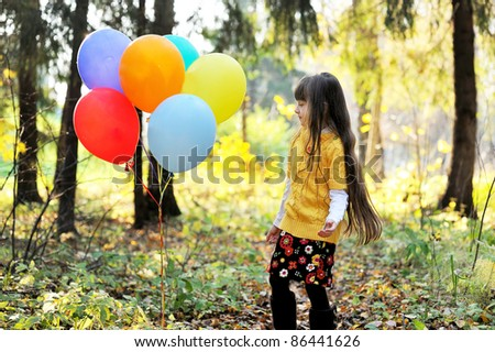 Child girl with colorful balloons playing alone in autumn forest - stock photo