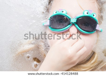 Child girl with diving goggles dive in the bath with foam - stock photo