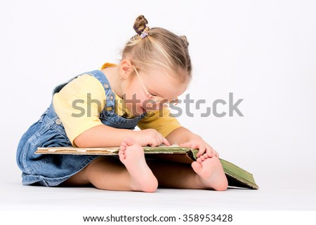 Child girl with glasses reading book on white background and floor. - stock photo