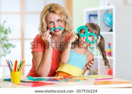 Child girl with mother have a fun cutting out scissors paper in preschool - stock photo