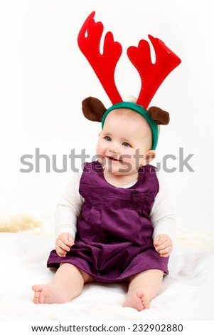 Child girl with reindeer antlers on white background - stock photo