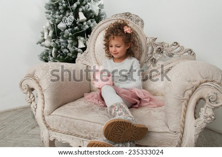 Child girl with sheep toy sitting on background of Christmas tree