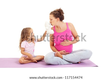 Child girl with teddy bear and her pregnant mother practicing yoga - stock photo