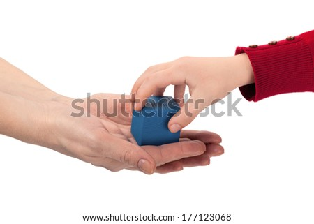 Child grabs blue wooden cube toy from mom's hands isolated on white background - stock photo