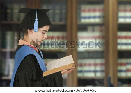 child graduation cap and books in the library - stock photo