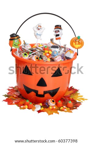 child halloween pumpkin bucket with candy and fall leaves - stock photo