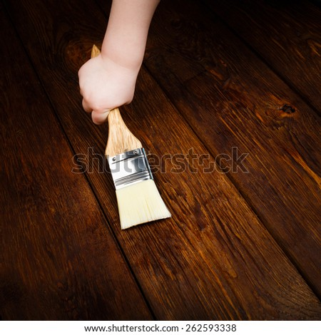 Child hand applying protective varnish on a wooden table with brush - stock photo