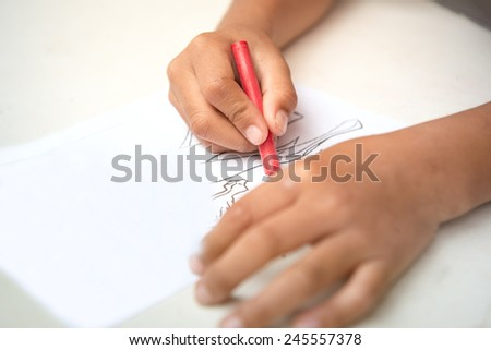 Child hand coloring on cartoon paper with color crayons - stock photo