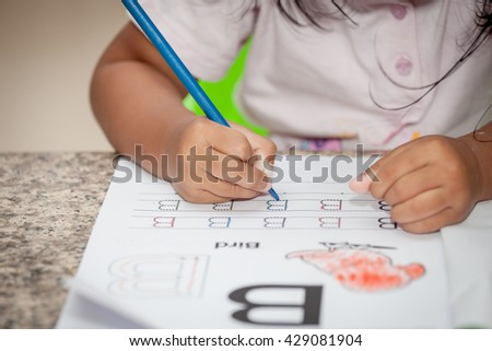 Child hand drawing her homework with crayon - stock photo