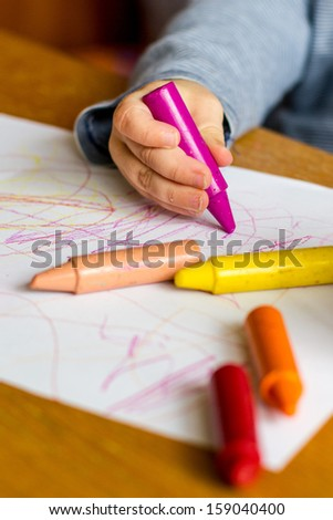 Child hand drawing with crayon