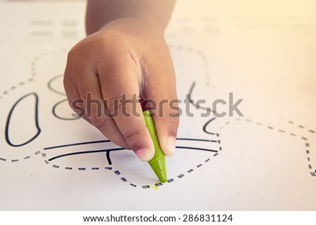 Child hand drawing with crayon,soft color filter - stock photo
