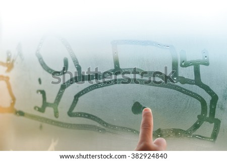 Child hand draws on fogged window, close up sign. Drops of rain on glass background - stock photo