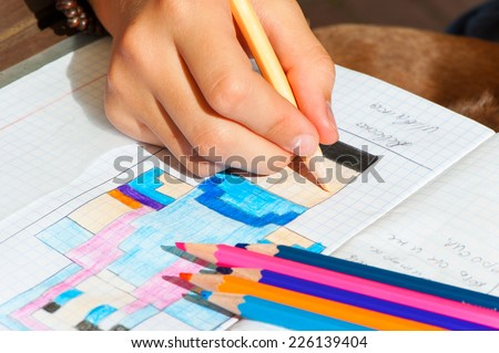 Child hand draws the multicolored minecraft picture. Outdoors close-up. - stock photo